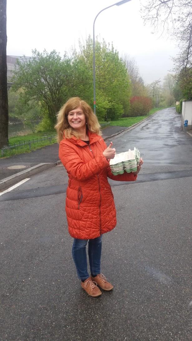 Barbara Tolliner steht mit Daumen hoch an der Übergabestelle der Eierkartons in Judendorf in Leoben